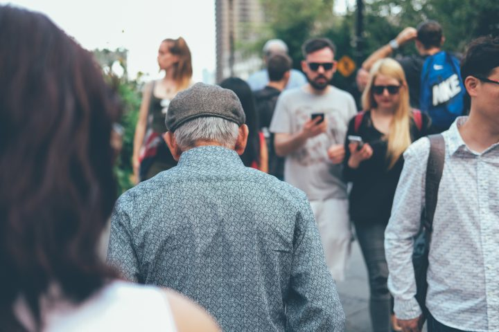 Old man in mobile savvy crowd